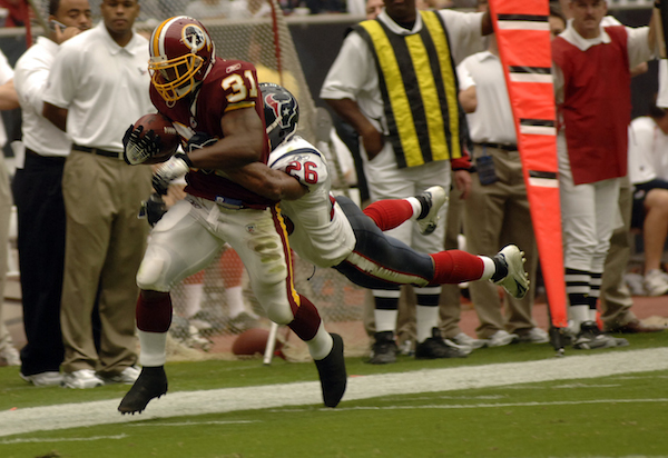 Washington Redskins running back Rock Cartwright is tackled by Houston Texans strong safety Glenn Earl during the Redskins 31-15 victory at Reliant Stadium in Houston Sept. 24. The Texans honored military servicemembers in their Salute to the Military day. (U.S. Air Force photo/Tech. Sgt. Cecilio M. Ricardo Jr.)