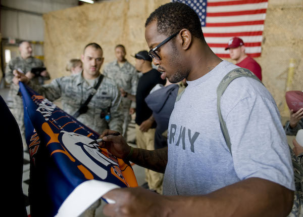 "Von Miller, National Football League Denver Broncos linebacker, signs a Broncos flag for Staff Sgt. Christopher Ingle, 376th Expeditionary Civil Engineer Squadron rescue engine 11 crew chief, March 20, 2013, at Transit Center at Manas, Kyrgyzstan. ""It's a great to see players from my favorite team,"" said Ingle. ""I was so excited when I found out they were visiting TCM."" Ingle is deployed from Peterson Air Force Base, Colo., and is a native of Clinton, Utah. (U.S. Air Force photo/Staff Sgt. Stephanie Rubi)"