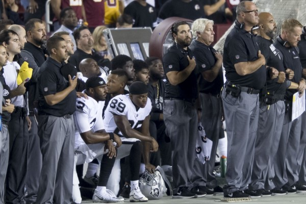Why do NFL players kneel during the National Anthem?